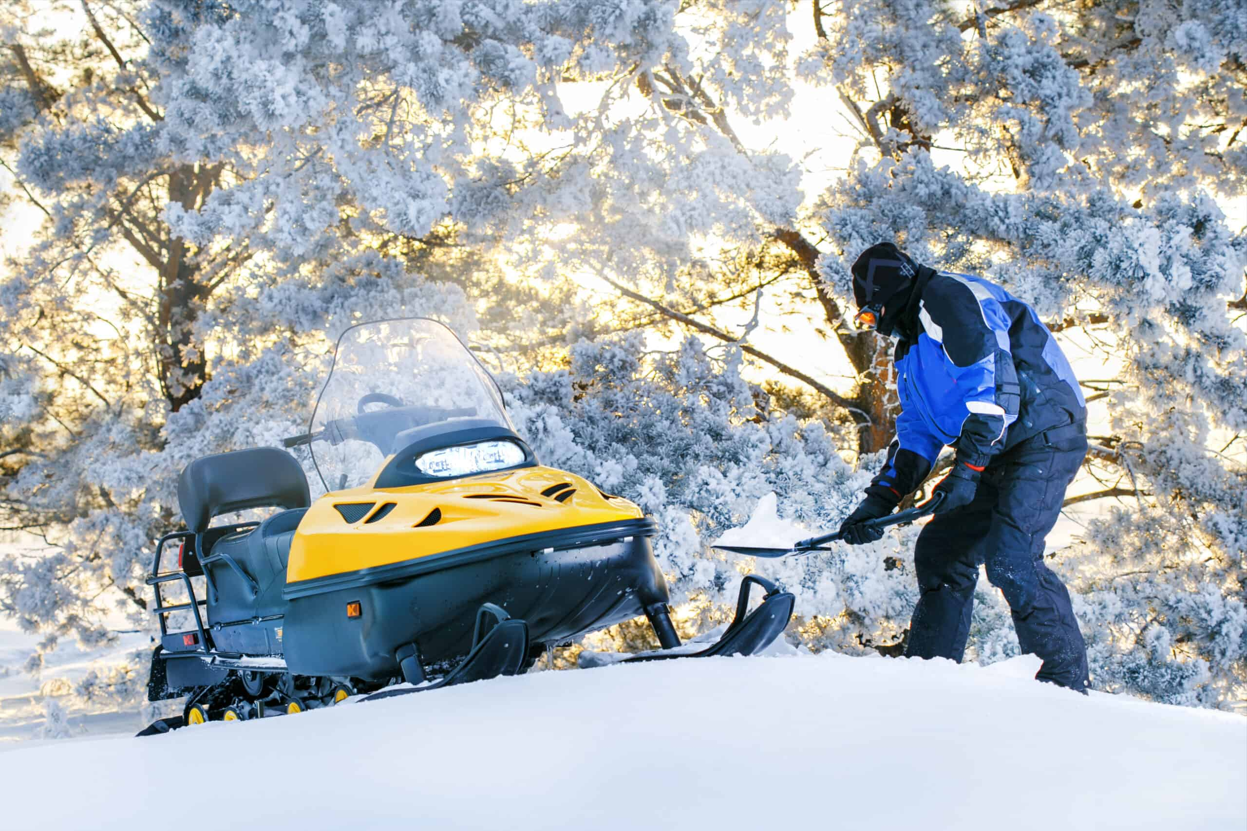 Man digging out Stuck Snowmobile